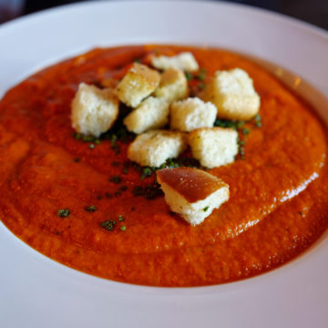 Pink tomato soup topped with crisp, cheey croutons