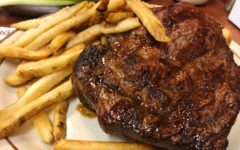 A big, juicy ribeye steak eclipses the bread that makes it a nominal sandwich