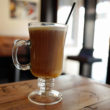 Tall glass cup holds tan coffee with a white, foamy head