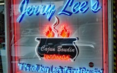 Neon window sign shows a boiling cauldron ... Cajun country boudin